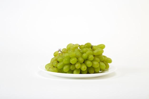 Reife grüne trauben auf einem weißen teller