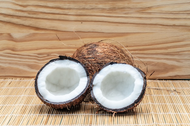 Reife hälfte schnitt kokosnuss auf einem hölzernen hintergrund
