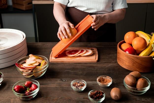 Reife hausfrau, die frische zitrusfrüchte über holzbrett durch küchentisch zwischen schalen mit gewürzen, kiwi, erdbeeren, orangen und banane schneidet