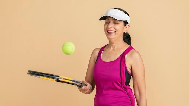 Reife indische tennisspielerin spielbereit