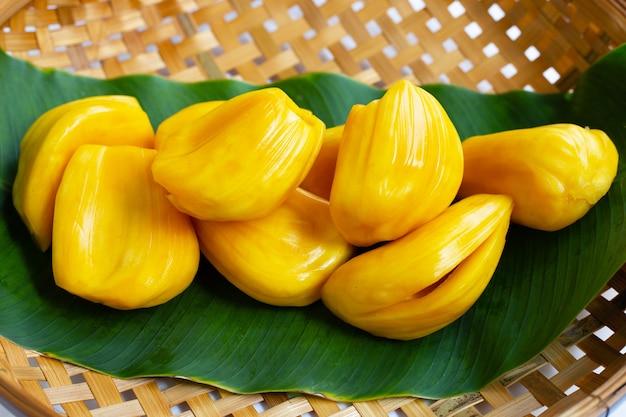 Reife jackfrucht auf bananenblatt im hölzernen bambusdreschkorb