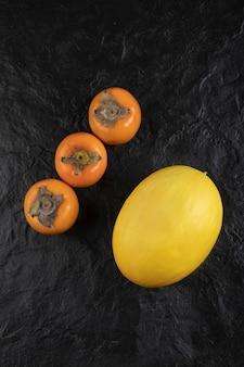 Reife kakifrüchte und leckere melone auf schwarzer oberfläche
