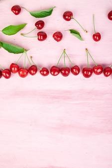 Reife kirschbeeren und kirschblatt auf rosa hintergrund