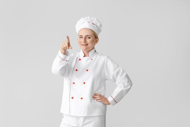Reife köchin, die auf etwas auf grau zeigt