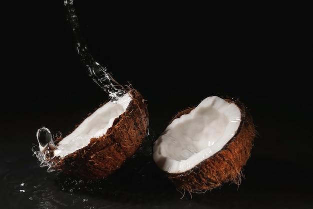 Reife kokosnuss und spritzer wasser im dunkeln