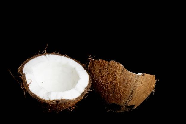 Reife kokosnuss wird in zwei hälften gebrochen, die auf einem schwarzen getrennt werden