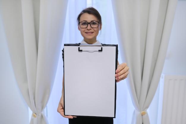 Reife lächelnde erfolgreiche geschäftsfrau, die leeres papier auf zwischenablage zeigt