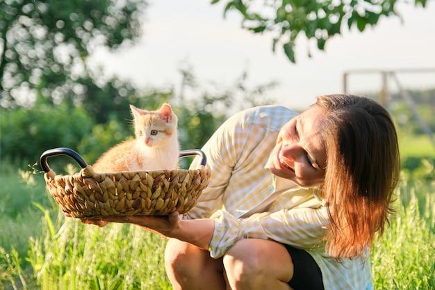 Reife lächelnde glückliche frau, die ingwer-kätzchen im korb, rustikalen stil, sonnigen frühlingssommertag im garten hält