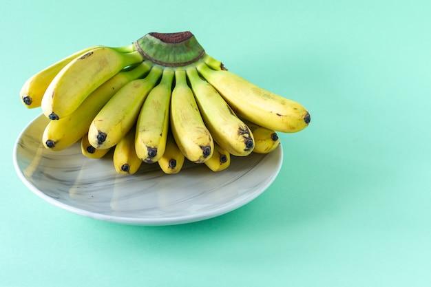 Reife leckere bananen auf einem teller auf blauem hintergrund. konzept für gesunde ernährung. Premium Fotos
