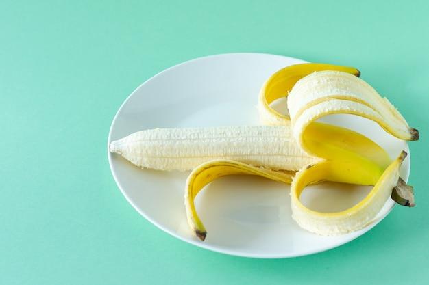 Reife leckere bananen auf einem teller auf blauem hintergrund. konzept für gesunde ernährung.