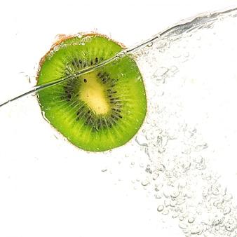 Reife leckere kiwi fällt in klares wasser