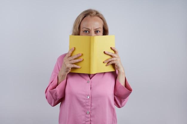Reife lehrerin, bibliothekarin in einem rosa hemd, hält ein gelbes buch und bedeckt ihr gesicht. lernkonzept.