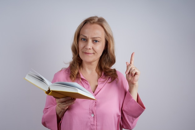 Reife lehrerin in einem rosa hemd, liest offenes buch, hält einen zeigefinger hoch. bildungskonzept.