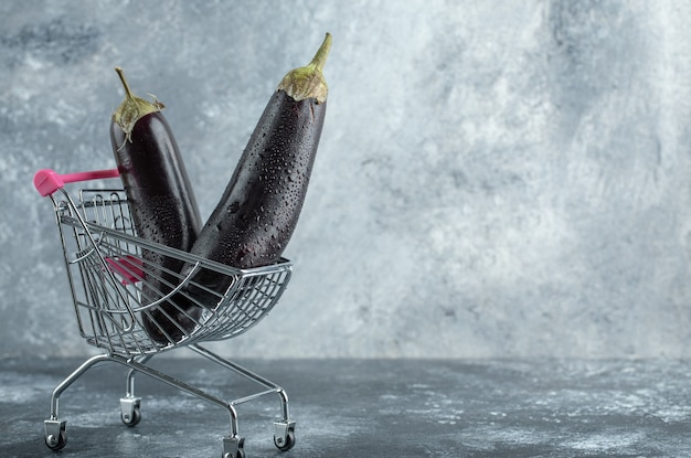 Reife lila auberginen im kleinen einkaufswagen