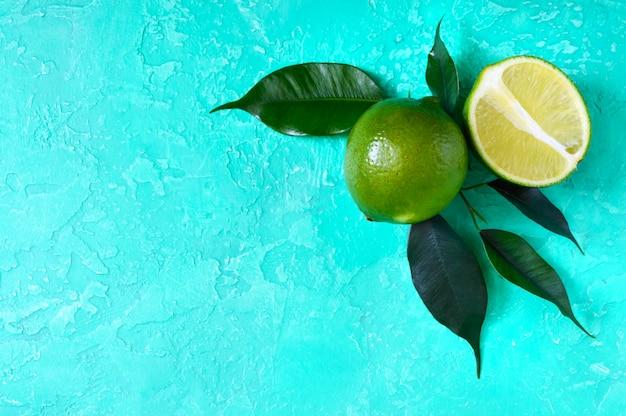 Reife limettenfrucht. ganze und geschnittene limette mit blättern. tropische exotische zitrusfrüchte. draufsicht. freier speicherplatz für ihr projekt.