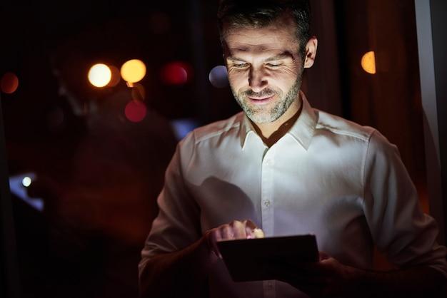 Reife männer, die nachts ein tablet benutzen