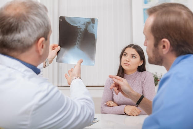 Reife männliche doktoren, die röntgenscan eines patienten überprüfen