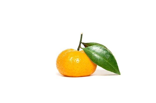 Reife mandarine mit grünen blättern auf weißem hintergrund