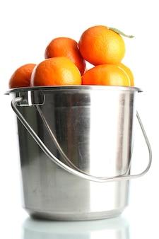 Reife mandarinen im blecheimer auf weiß
