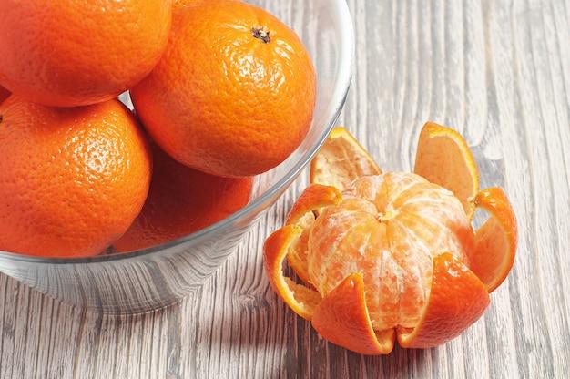 Reife mandarinen in glasschale auf rustikalem holztisch