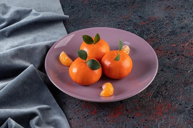 Reife mandarinen mit blättern auf einem lila teller.