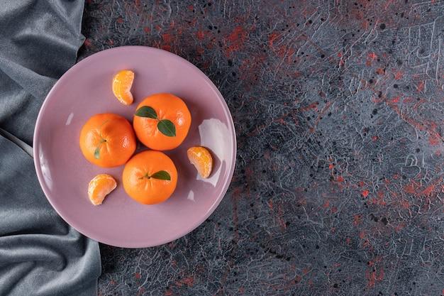 Reife mandarinen mit blättern auf einem lila teller