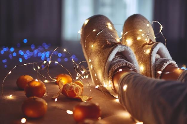Reife mandarinen orange, warmweiße weihnachtslichtgirlande und weibliche beine tragen warme flauschige weiche winterpantoffeln am gemütlichen zuhause am heiligabend