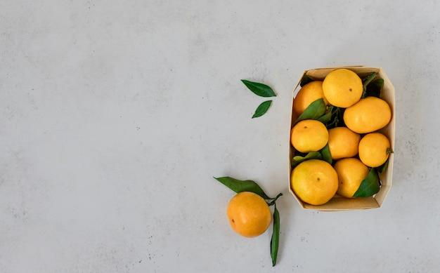 Reife mandarinen, zitrusfrüchte mit blättern in einem korb.