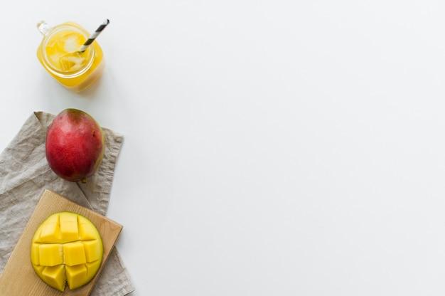 Reife mango, halbe mango und ein glas mangosaft auf einem hölzernen schneidebrett.