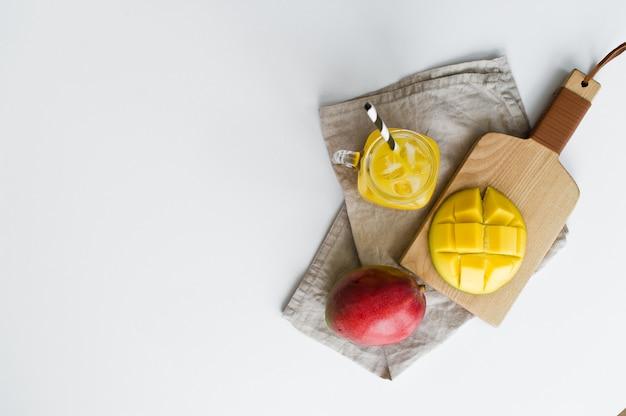 Reife mango, halbe mango und ein glas mangosaft mit einem rohr auf einem hölzernen schneidebrett.