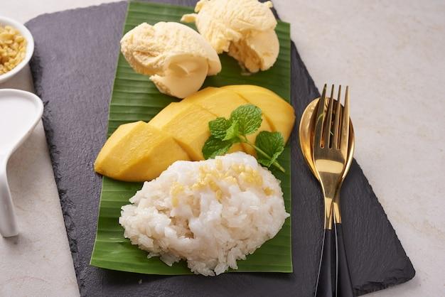 Reife mango und klebreis, eis mit kokosmilch auf steinoberfläche, thailändisches süßes dessert in der sommersaison. tropische frucht. dessertfrucht. draufsicht.