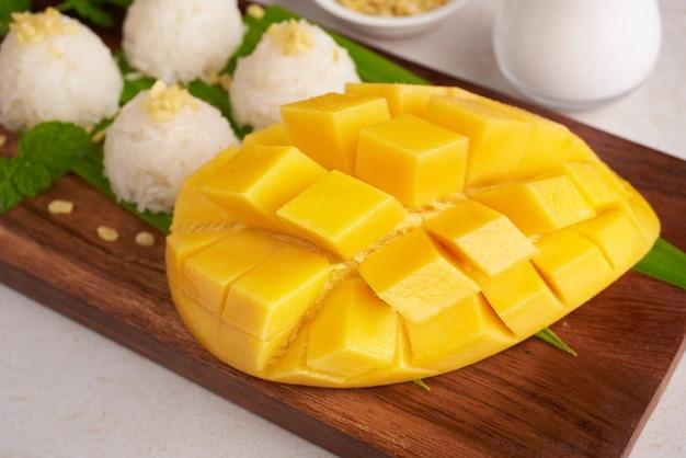 Reife mango und klebreis mit kokosmilch auf holzteller auf steinoberfläche, tropische frucht. dessertfrucht. thailändisches süßes dessert auf sommersaison.