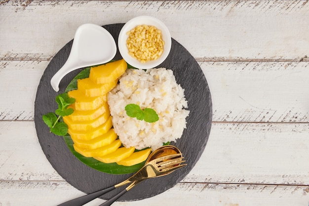 Reife mango und klebreis mit kokosmilch auf steinoberfläche, thailändisches süßes dessert in der sommersaison.