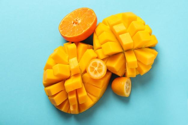 Reife mango und orange auf blauem hintergrund.