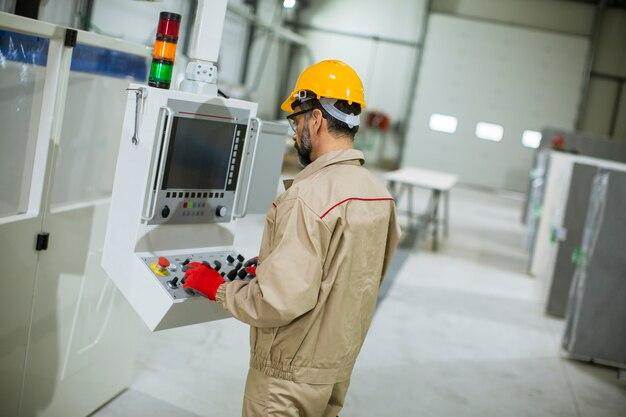 Reife mann, die maschineneinheiten in der modernen fabrik bedient, die durch bedienfeld bereitsteht