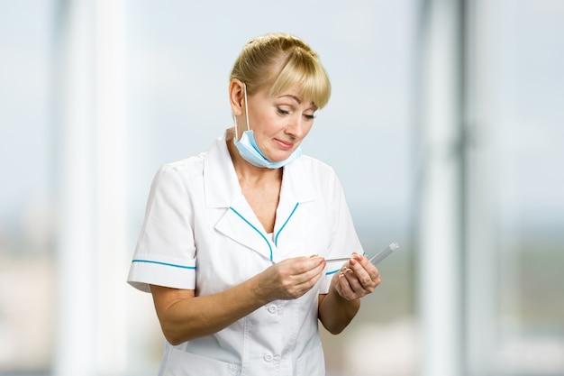 Reife medizinische ärztin, die auf thermometer schaut. blonde krankenschwester mittleren alters, die überraschend auf termometer schaut.