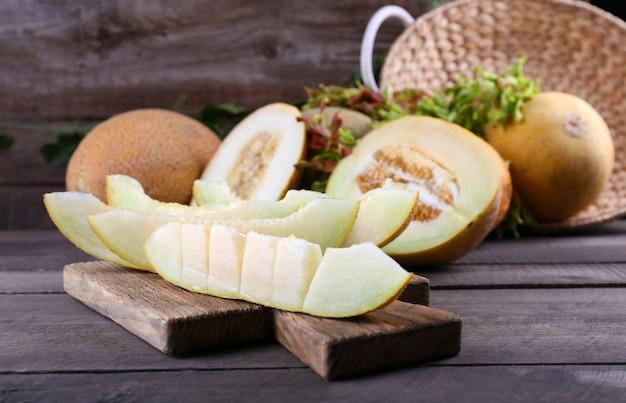 Reife melonen mit grünen blättern auf tischnahaufnahme