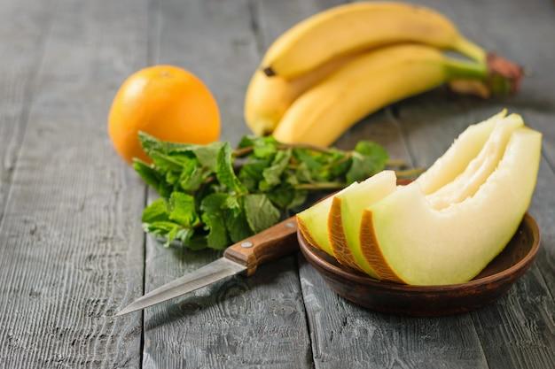 Reife melonenstücke auf einer tonschale, banane, minze, messer und orange auf einem rustikalen schwarzen tisch.