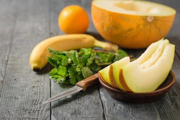 Reife melonenstücke auf einer tonschale, banane, minze, orange und messer auf einem holztisch.