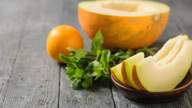 Reife melonenstücke auf einer tonschale, banane, minze und orange auf einem rustikalen holztisch.
