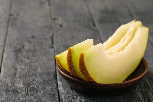 Reife melonenstücke auf einer tonschale einen holztisch.