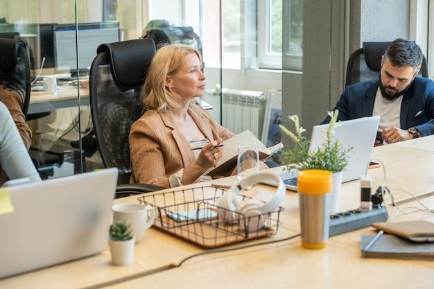 Reife nachdenkliche blonde geschäftsfrau mit offenem notizbuch, das im sessel vor schreibtisch sitzt und über arbeitspunkte nachdenkt