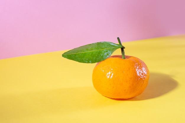 Reife orange mandarine mit blatt auf gelb und rosa in isometrischer