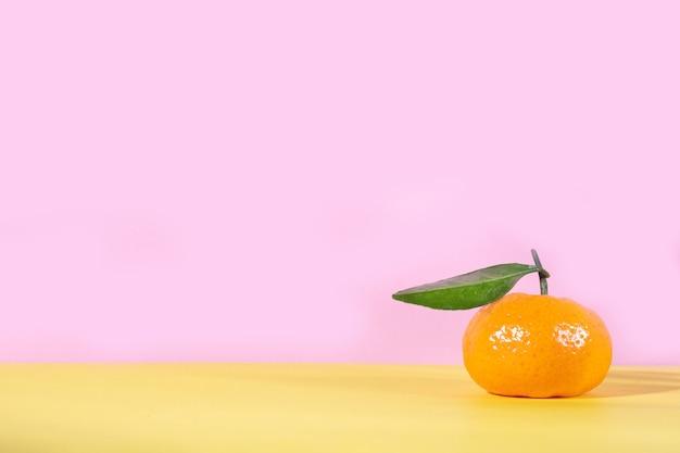 Reife orange mandarine mit blatt auf rosa und gelb