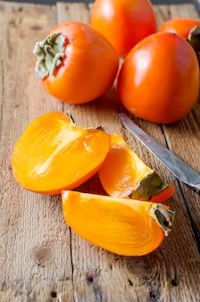 Reife orange persimonen auf einem alten holztisch