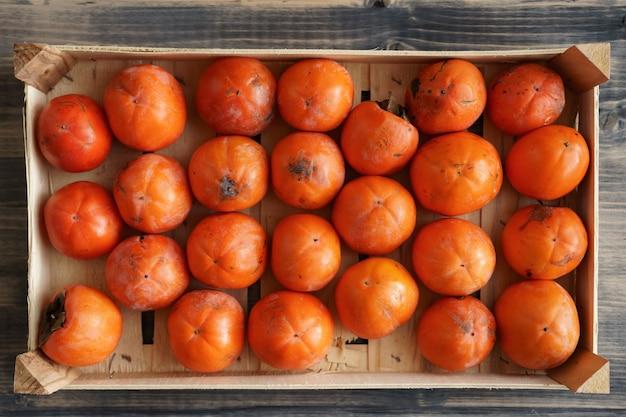 Reife orangefarbene kakis in einer schublade, die textur des hintergrunds ist von kakifrüchten