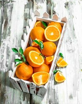 Reife orangen in der schachtel auf weißem holztisch
