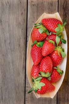 Reife organische erdbeeren in der birkenrinde rollen auf dunklem hölzernem hintergrund
