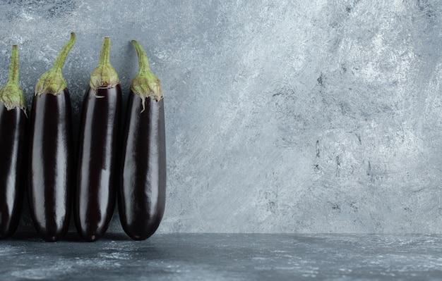 Reife organische lila auberginen auf grauem hintergrund.
