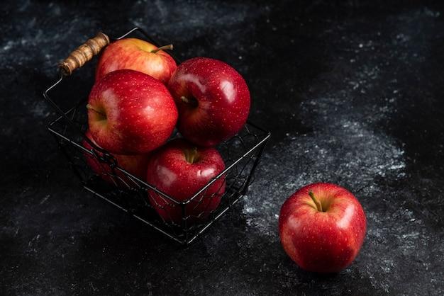Reife organische rote äpfel im metallkorb auf schwarzer oberfläche. .